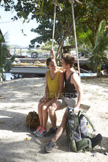 Couple with backpacks sitting on swing — Stock Photo
