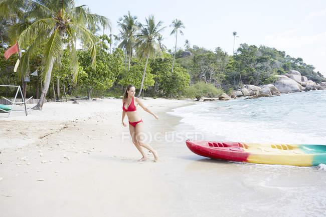 Frau ziehen Kajak am Strand — Stockfoto