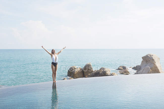 Woman with her arms raised standing by pool — Stock Photo