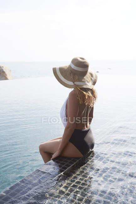 Woman sitting in swimming pool — Stock Photo