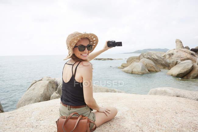 Frau mit Sonnenbrille und Kamera auf Felsen — Stockfoto