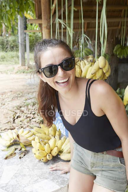 Femme souriant près d'un tas de bananes — Photo de stock