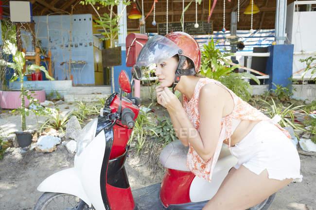 Woman putting on helmet on moped — Stock Photo