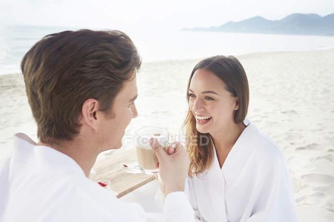 Couple drinking coffee on beach — Stock Photo