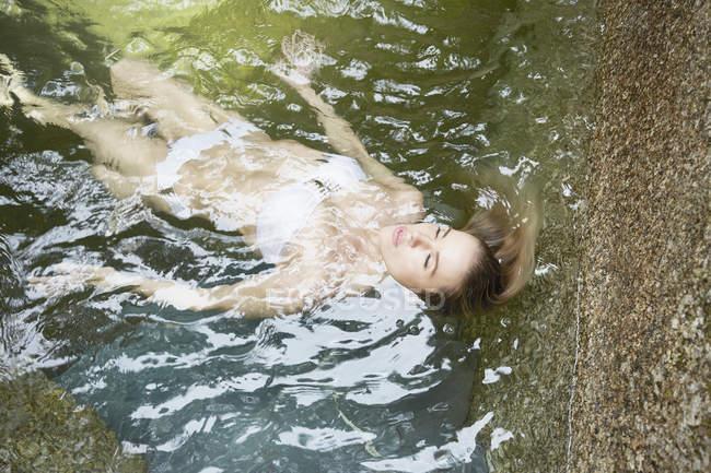 Mulher boiando na piscina — Fotografia de Stock