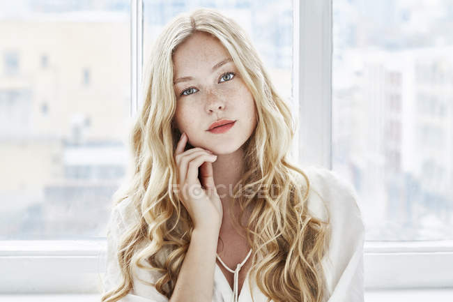 Woman with blonde hair touching face — Stock Photo