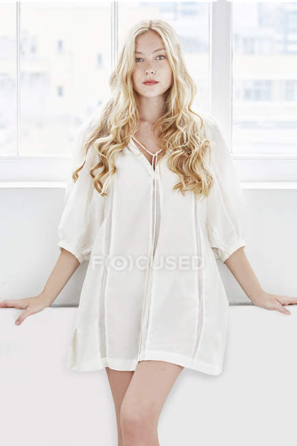 Woman with blonde hair wearing white tunic — Stock Photo