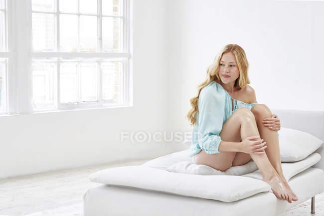 Mulher sentada no sofá tocando as pernas — Fotografia de Stock