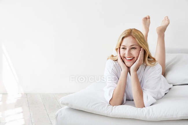 Woman lying on front with hands on chin — Stock Photo