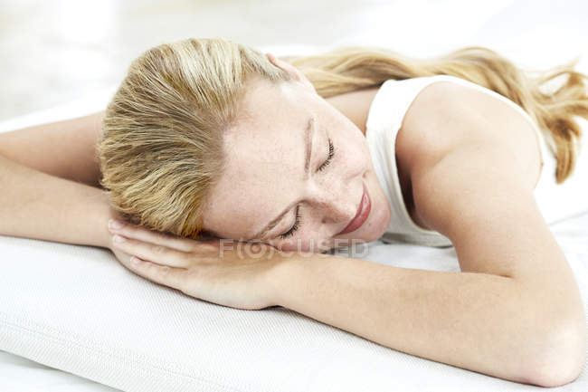 Woman lying on front with eyes closed — Stock Photo
