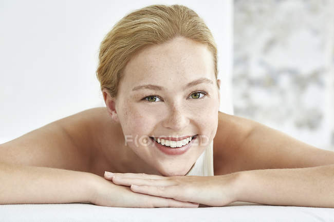Woman lying on front and smiling at camera — Stock Photo
