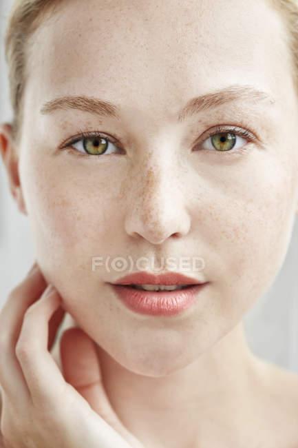 Mujer tocando la cara y mirando a cámara - foto de stock