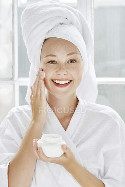 Woman applying moisturiser to face — Stock Photo