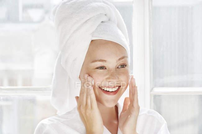 Woman applying moisturiser to face — Stock Photo