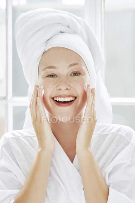 Frau anwenden Feuchtigkeitscreme Gesicht — Stockfoto