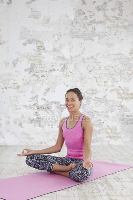 Woman sitting cross legged on mat — Stock Photo