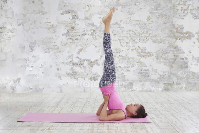 Женщина на коврике с поднятыми ногами — стоковое фото