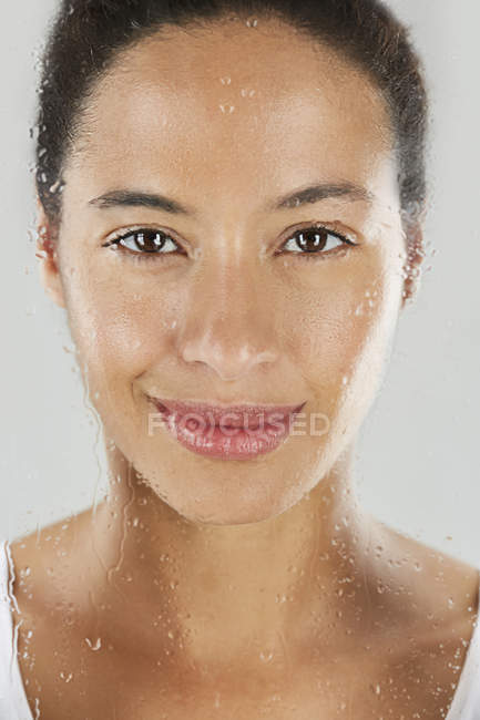 Woman through wet glass — Stock Photo