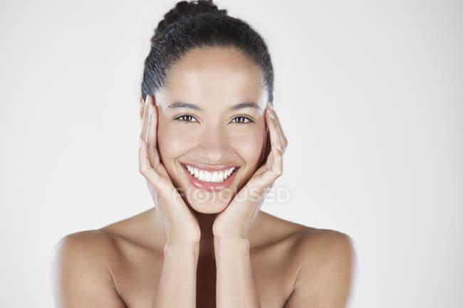 Mulher com as mãos, tocar o rosto e sorrir — Fotografia de Stock