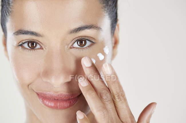 Aplicar Crema de cara de mujer - foto de stock