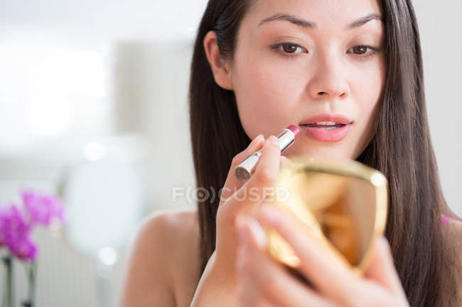 Donna che applica rossetto con specchio compatto — Foto stock