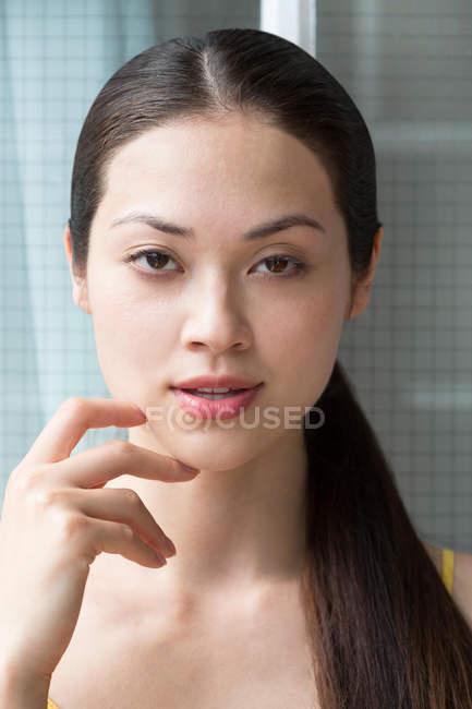 Mujer con el dedo en la barbilla - foto de stock