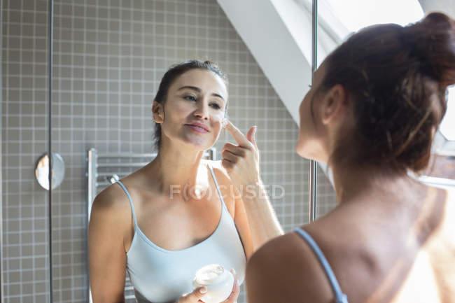 Woman applying moisturiser — Stock Photo