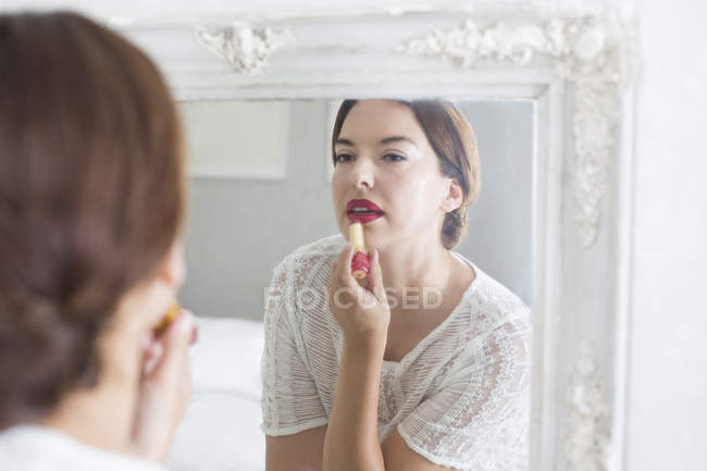 Woman applying make-up in mirror — Stock Photo