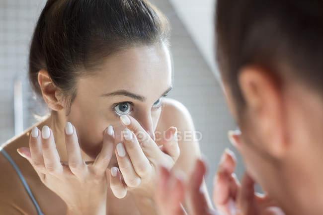 Mujer aplicando lente de contacto - foto de stock