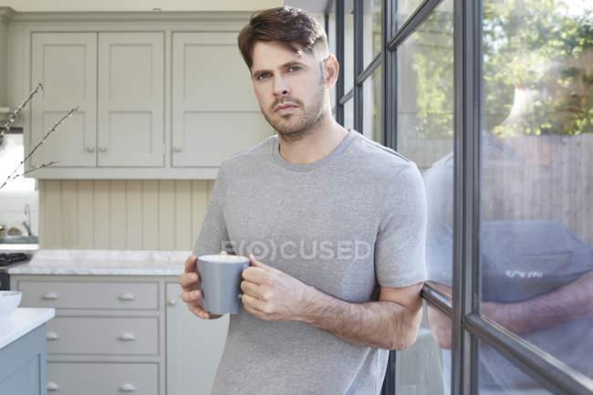 Homme tenant une tasse de café — Photo de stock