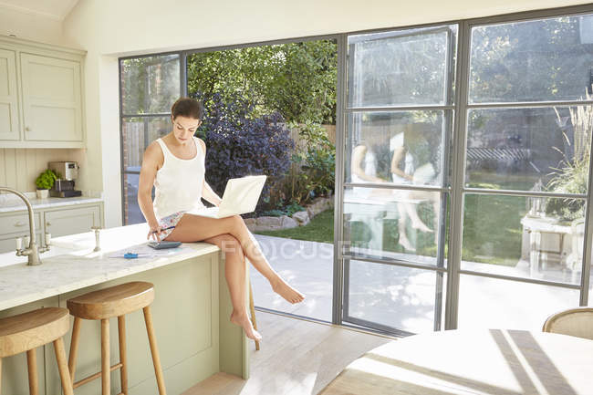 Жінка користується ноутбуком на кухні. — стокове фото
