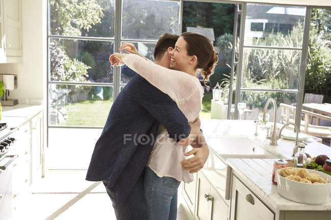 Pareja abrazándose en cocina - foto de stock