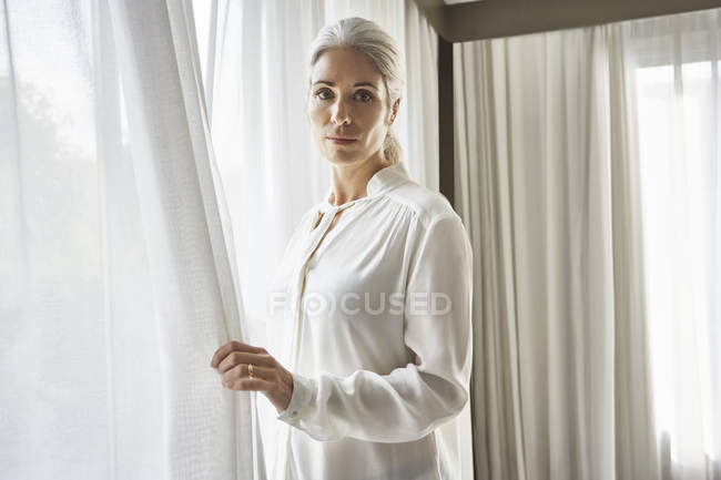 Woman standing at window and looking at camera — Stock Photo