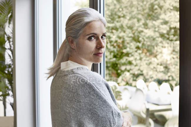 Mulher de pé na janela e olhando para a câmera — Fotografia de Stock