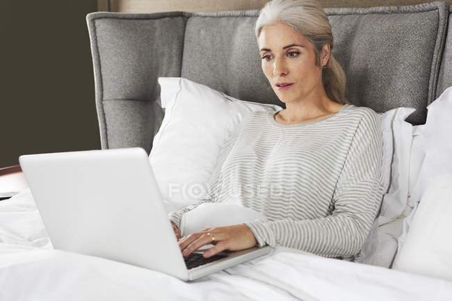 Femme travaillant avec un ordinateur portable au lit — Photo de stock