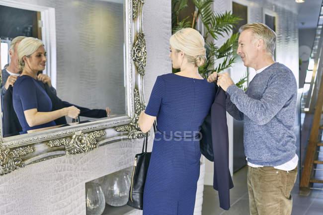 Mann hilft Frau mit Blazer — Stockfoto