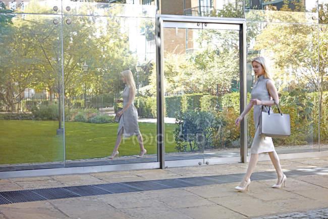 Предприниматель, ходить рядом с Светоотражающий окна — стоковое фото