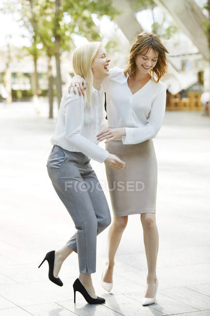 Women laughing together in park — Stock Photo