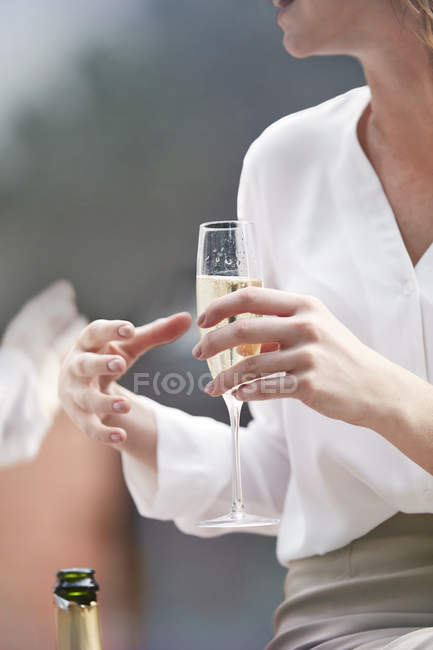 Woman holding champagne flute — Stock Photo