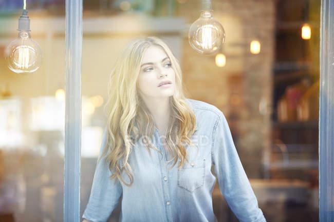 Mulher olhando pela janela — Fotografia de Stock
