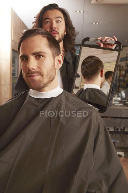 Uomo che si guarda allo specchio in barbiere — Foto stock