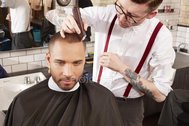 Парикмахер стрижет клиентов — стоковое фото
