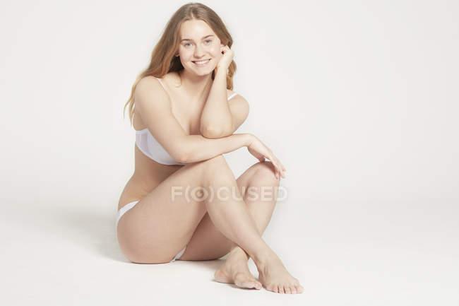 Woman sitting in white underwear — Stock Photo