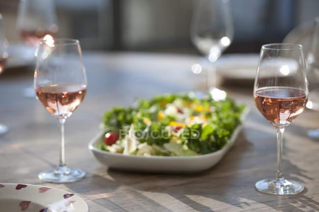 Salat und Wein auf dem Esstisch — Stockfoto