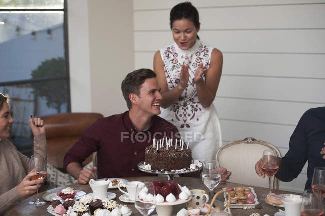Friends celebrating with birthday cake — Stock Photo