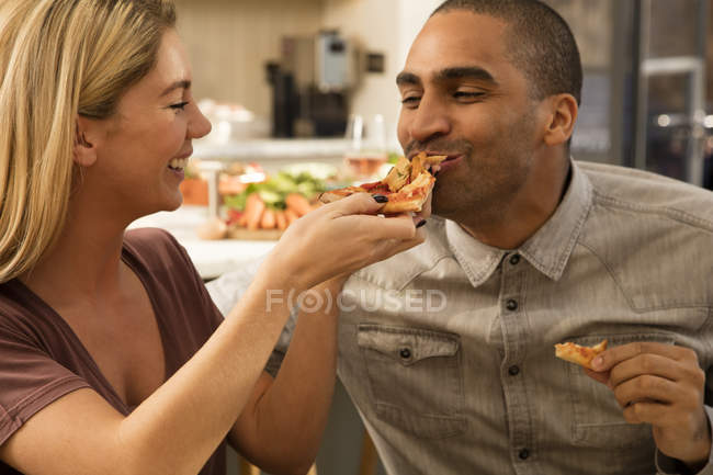 Woman feeding pizza to boyfriend — Stock Photo