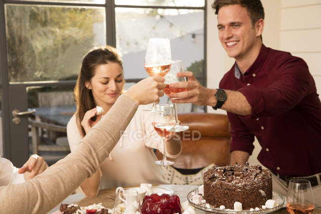Friends celebrating with chocolate birthday cake — Stock Photo