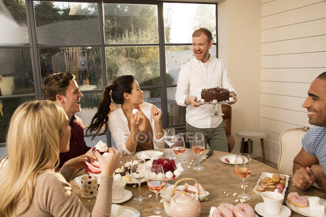 Friends celebrating with chocolate birthday cake — Stock Photo