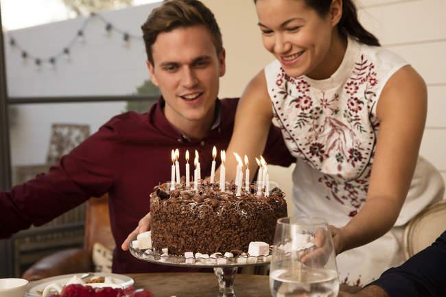 Женщина показывает мужчине торт на день рождения — стоковое фото