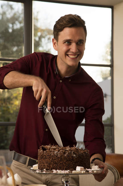 Man cutting chocolate birthday cake — Stock Photo